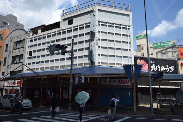 かつて衣料品店だった建物は居酒屋「寅八」に変わったが「1F LADIES'」などの看板がそのまま