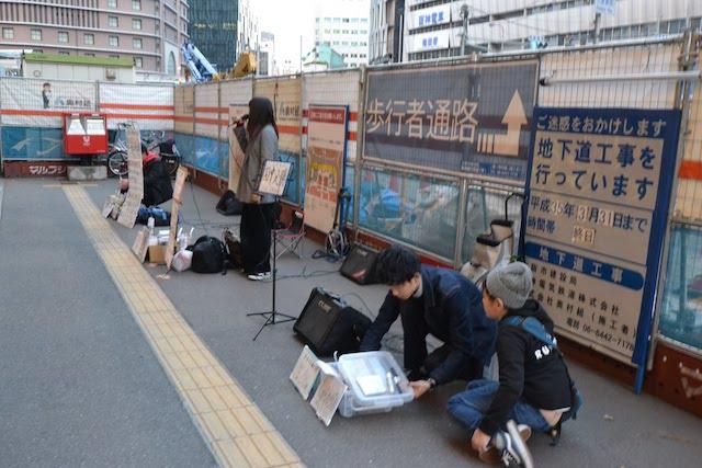 大阪駅中央南口の工事仮囲い前で演じるストリートミュージシャン