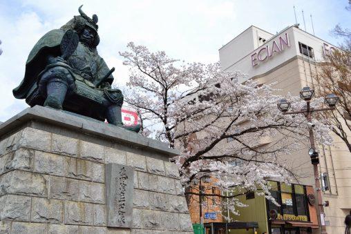 桜咲く季節の武田信玄公銅像(駅ビルは旧「エクラン」)